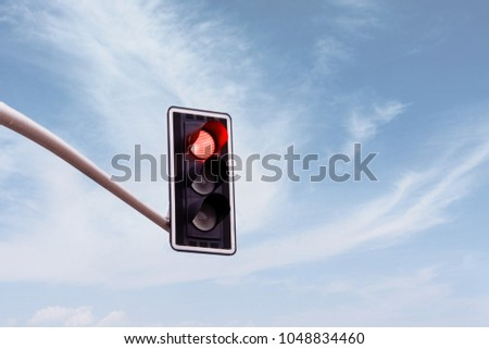 Red traffic light on a horizontal white metal beam, isolated on sky background - Shutterstock ID 1048834460