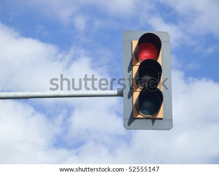 Red traffic light on sky