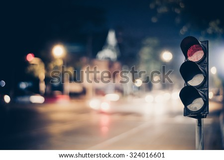 Red traffic light on the road during the night. light sign for car stop and speed reduction. Dangerous,warning signal,semaphore driving.