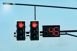 Red traffic lights with countdown numbers under the sky.