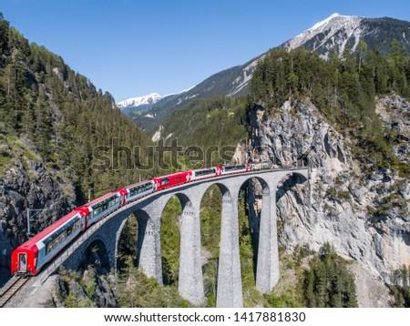 Red train of Bernina Express on the Landwasser viaduct. Unesco World Heritage in the Swiss Alps. Filisur - Albula