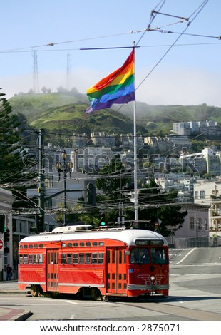 Red tram car under rainbow flag in Castro, San Francisco