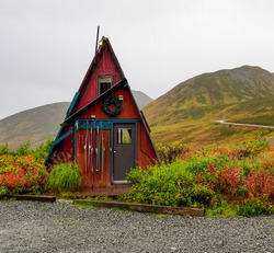 Red Triangle Dry Cabin In Hatcher Pass Surrounded By Mountains Full Of Fall Colors On A Rainy Day In Alaska