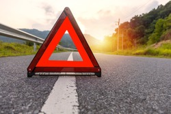 Red triangle, red emergency stop sign, red emergency symbol on road with sun light background.