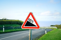 Red triangle road sign indicating a steep 10 percent downhill gradient in the road ahead. Empty road with crash barriers surrounded by green grass in the background. Traffic signs.
