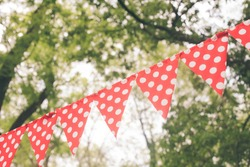 Red triangular flags with white dots on the nature background