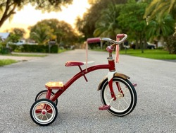 Red tricycle white wheels. Classic vintage childhood bicycle. Traditional tricycle