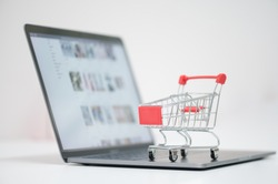 Red trolley on laptop keyboard.A cart and notebook computer on white background.Electronic commerce that allows consumers to directly buy goods from a seller over the internet.Shopping online concept.