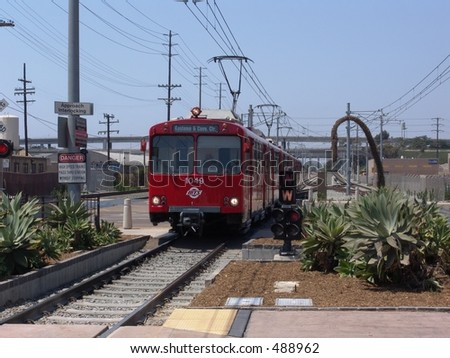 Red trolley pulling into a station, bound for San Diego's Gaslamp district