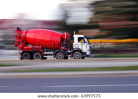 Red truck concrete mixer, panning and blur