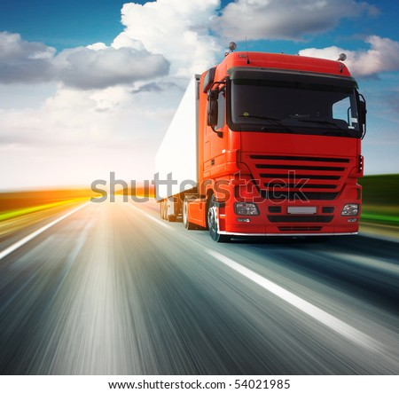 Red truck on blurry asphalt road over blue cloudy sky background #54021985