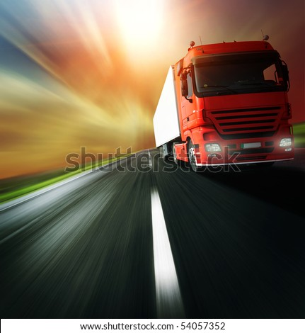 Red truck on blurry asphalt road over cloudy sky background