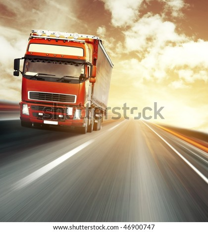 Red truck on blurry asphalt road under red sky with clouds and sunset light