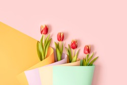 Red tulip flowers in a bouquet made of colorful wallpaper arange in diagonal. Creative background spring concept.