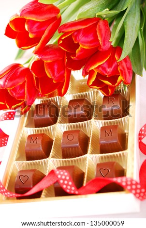 red tulips and box of chocolates as gift for mother
