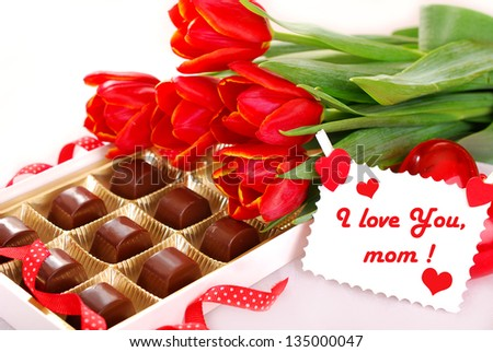 red tulips and box of chocolates with greeting card as gift for mother
