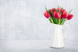Red tulips bouquet in front of wooden wall. With space for your text