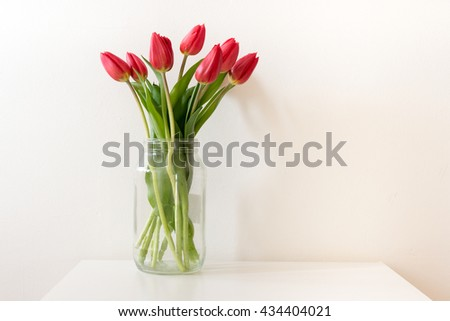 Red tulips in tall glass jar on white table against white wall #434404021