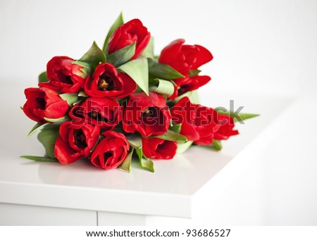 red tulips lying on white table