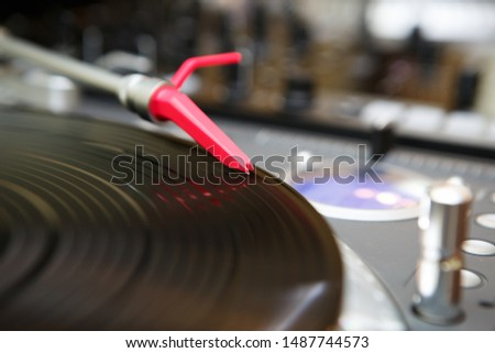 Red turntables needle on tone arm.Professional dj turn table player with old analog record in close up.Concert stage equipment for disc jockey.High quality audio setup for night club performance