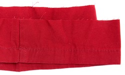 Red twill sample textile showing seam allowance and tattered threads, isolated in white background