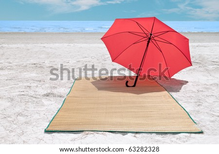 Red umbrella and bamboo mat on the beach