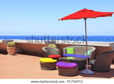 Red umbrella and summer armchairs with color pillows on a roof against Mediterranean sea and the blue sky