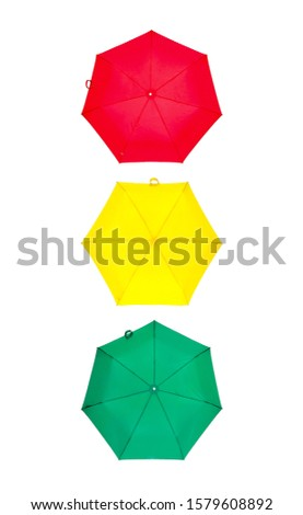 Red umbrella, green umbrella and yellow umbrella in form of traffic light isolated on white