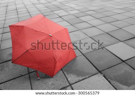 Red umbrella on the floor wet after rain.