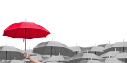 red umbrella over dark umbrellas on white background. The difference to step up to leadership in business.hand of man holding a red umbrella in raining. side view.