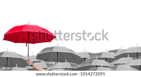 red umbrella over dark umbrellas on white background. The difference to step up to leadership in business.hand of man holding a red umbrella in raining. side view. #1054272095