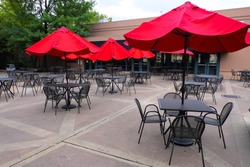 Red umbrella with black chairs and tables in outdoor public park restaurant.