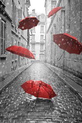 Red umbrellas flying on the street. Conceptual, surreal image.