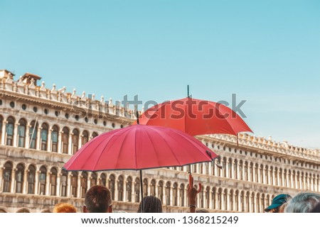 Red umbrellas of tour guides conducting tours on the background of the Piazza San Marco in Venice. Tourist destination. #1368215249
