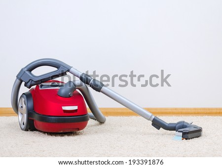 Red vacuum cleaner in empty room.