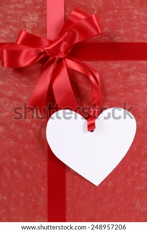 Red valentine gift background with ribbon, bow and heart shape gift tag.  Space for copy.