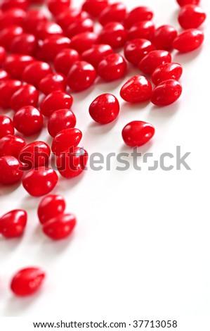 Red Valentine's cinnamon heart candies on white background