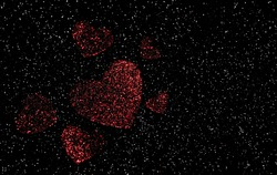 Red Valentine's day hearts that are faded shown with a glittery black background with white dots