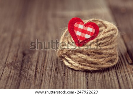 Red valentine\'s day holiday heart in nest on wooden background with retro instagram toning