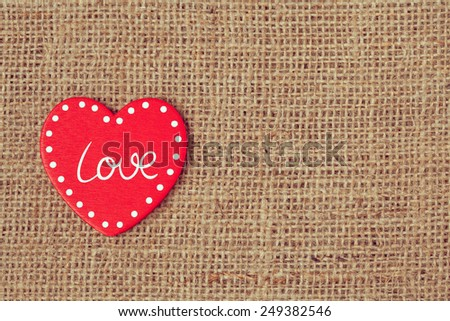 Red valentine\'s day holiday heart on retro textile background with vintage instagram toning