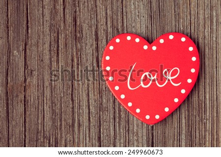 Red valentine\'s day holiday heart  on retro wooden background with vintage instagram toning