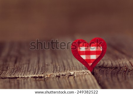 Red valentine\'s day holiday heart  on wooden background with vintage instagram toning