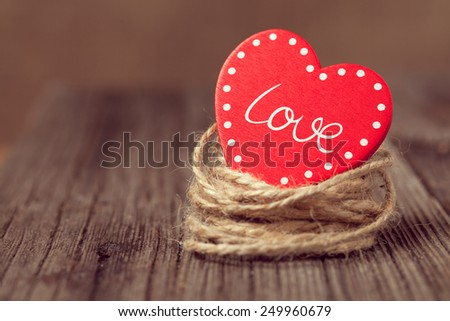 Red valentine\'s day holiday heart with text in nest on wooden background with vintage instagram toning