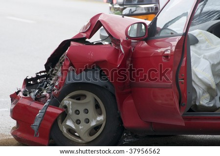 Red vehicle with smashed front end showing air bag deployment