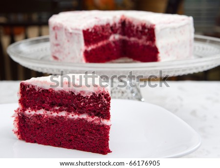 red velvet cake on a glass platter with one slice removed in front