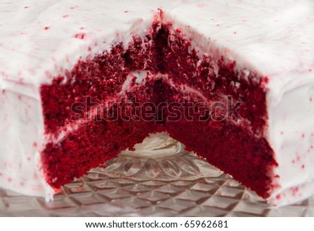 red velvet cake with one slice removed on a glass platter