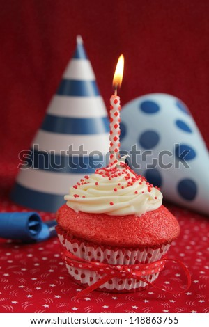Red velvet cupcake with blue birthday hats on a red background