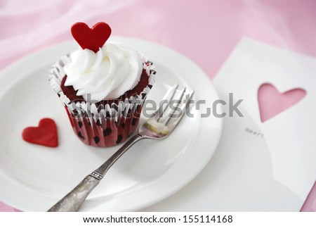 Red velvet cupcake with vanilla icing decorated with a red heart made of chocolate