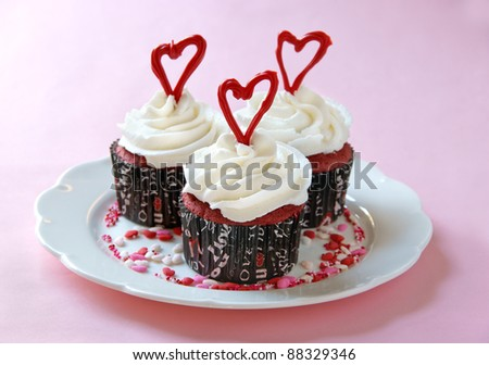 Red Velvet cupcakes with cream cheese frosting, decorated for Valentine's Day.