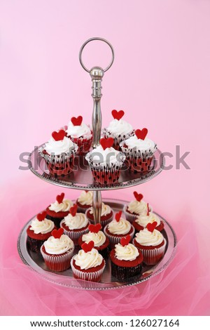 Red velvet cupcakes with cream cheese on a two tier cake stand